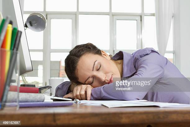 Woman at home sleeping at desk with computer