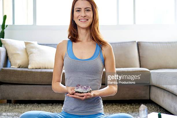 Woman at home smiling with crystals in hand