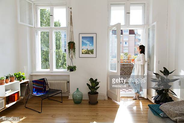 woman at home standing at balcony door - balcony stock pictures, royalty-free photos & images