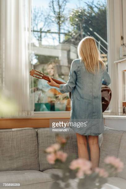 Woman at home standing on couch looking out of window