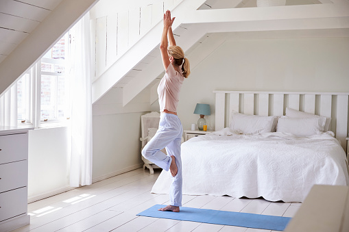 Woman At Home Starting Morning With Yoga Exercises In Bedroom 846715326