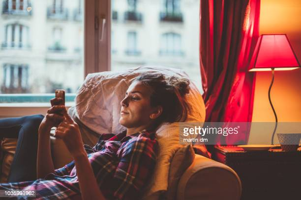 woman at home texting on phone - electric lamp stock pictures, royalty-free photos & images