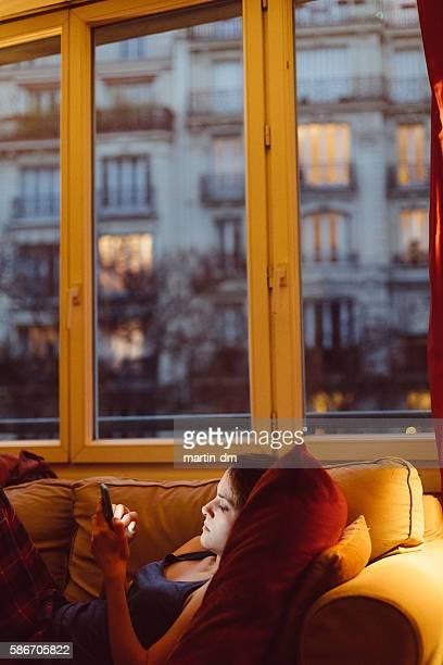 Femme à la maison à envoyer des SMS sur le téléphone