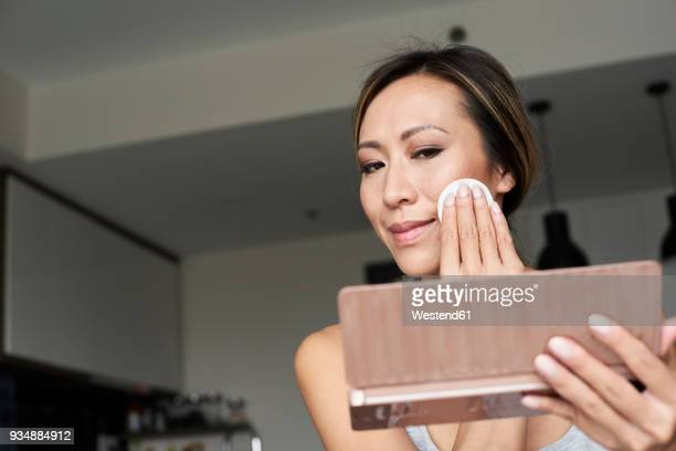 Woman at home using hand mirror removing makeup with cotton pad