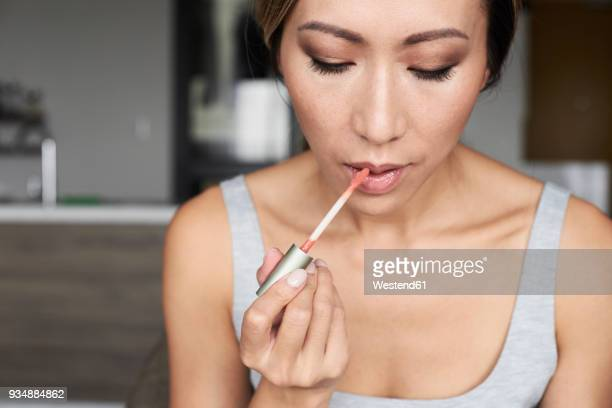woman at home using makeup applying lip gloss - lip gloss stock pictures, royalty-free photos & images
