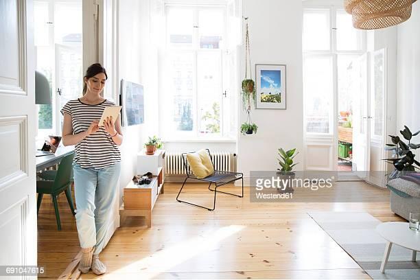woman at home using tablet - une seule femme d'âge moyen photos et images de collection