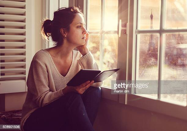 Woman at home watching Paris cityscape through the window