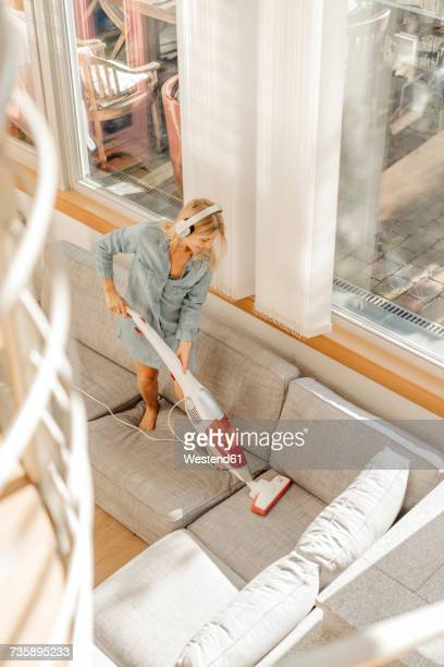 Woman at home wearing headphones hoovering the couch