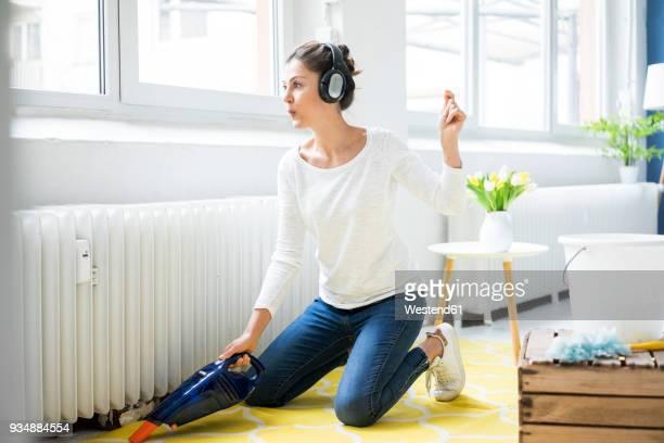 woman at home wearing headphones hoovering the floor - reinigen stock-fotos und bilder