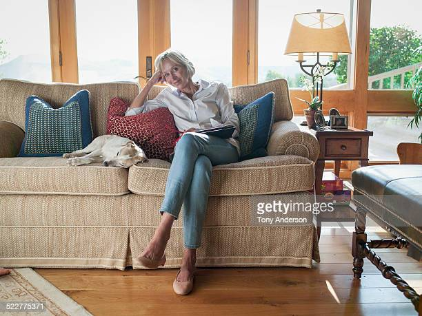 Woman at home with her reading and dog