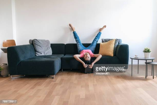 woman at home with tablet lying on sofa upside down - lying down stock-fotos und bilder