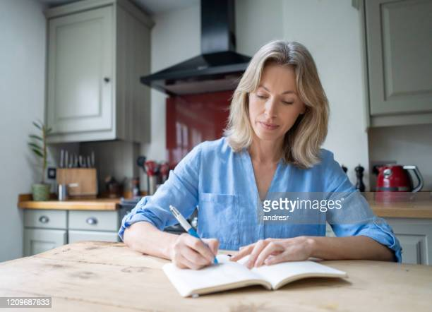 woman at home writing on her journal - writer stock pictures, royalty-free photos & images