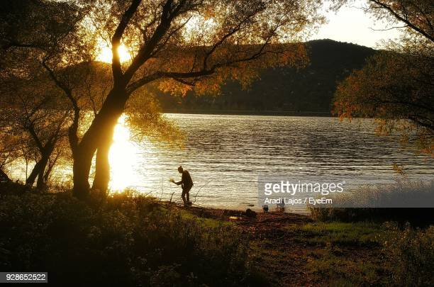 Woman At Lake Against Sky During Sunset