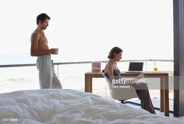 woman at laptop and man in room with large windows - big tom stock pictures, royalty-free photos & images