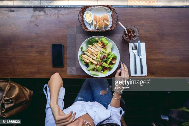 Woman at lunch break sitting in outdoor restaurant bar