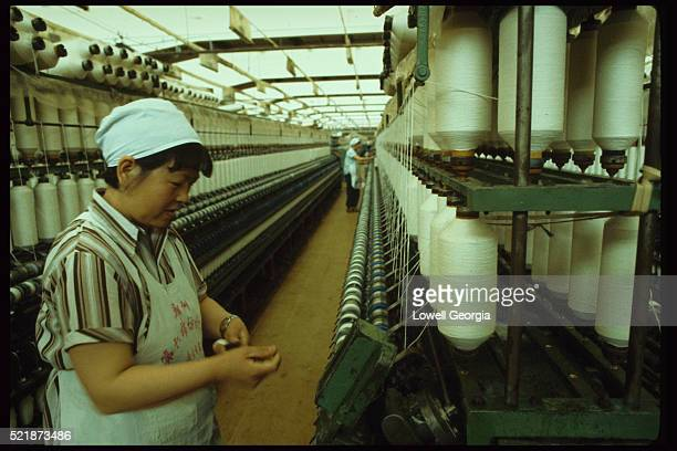 Woman at Machine Spinning Cotton Spools