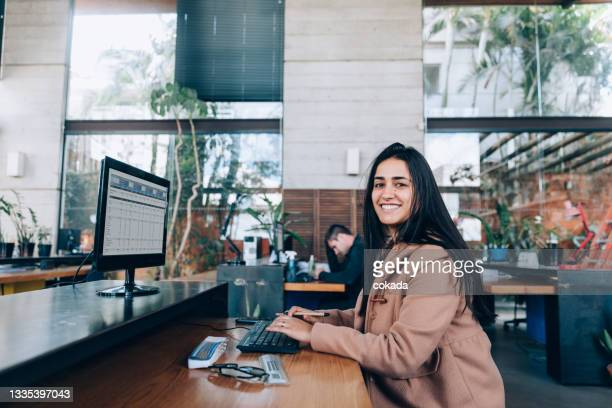 woman at office lloking at the camera - economist stock pictures, royalty-free photos & images