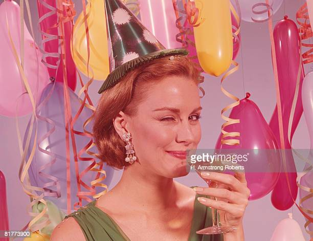 Woman at party, wearing party hat and winking, holding glass of wine. (Photo by H. Armstrong Roberts/Retrofile/Getty Images)