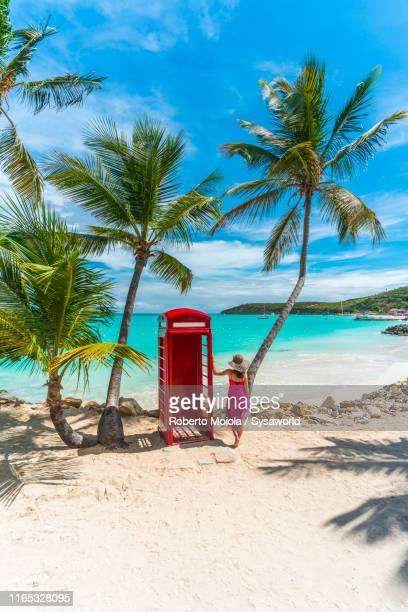 woman at phone box, siboney beach, dickenson bay, antigua - barbados stock pictures, royalty-free photos & images