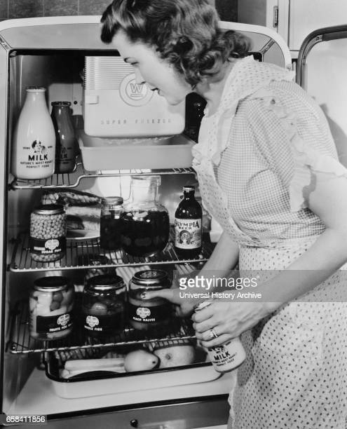Woman at Refrigerator filled with Food Products in Glass Jars due to Restriction of Metal Products because of Military Needs during World War II USA...