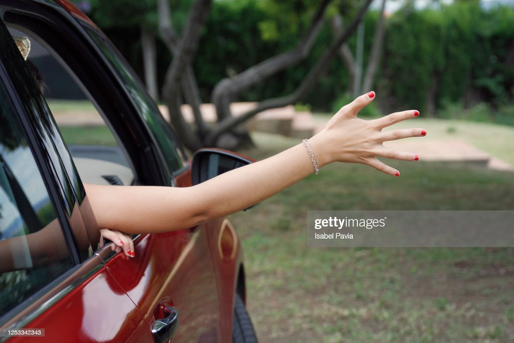 Woman at road trip enjoying with hand on the road breeze : Stock Photo