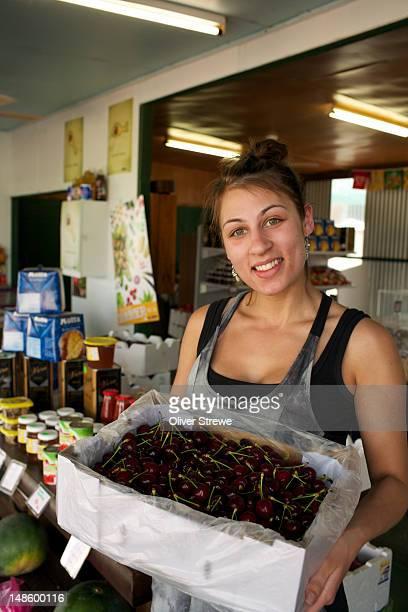 Woman at roadside stall selling cherries.