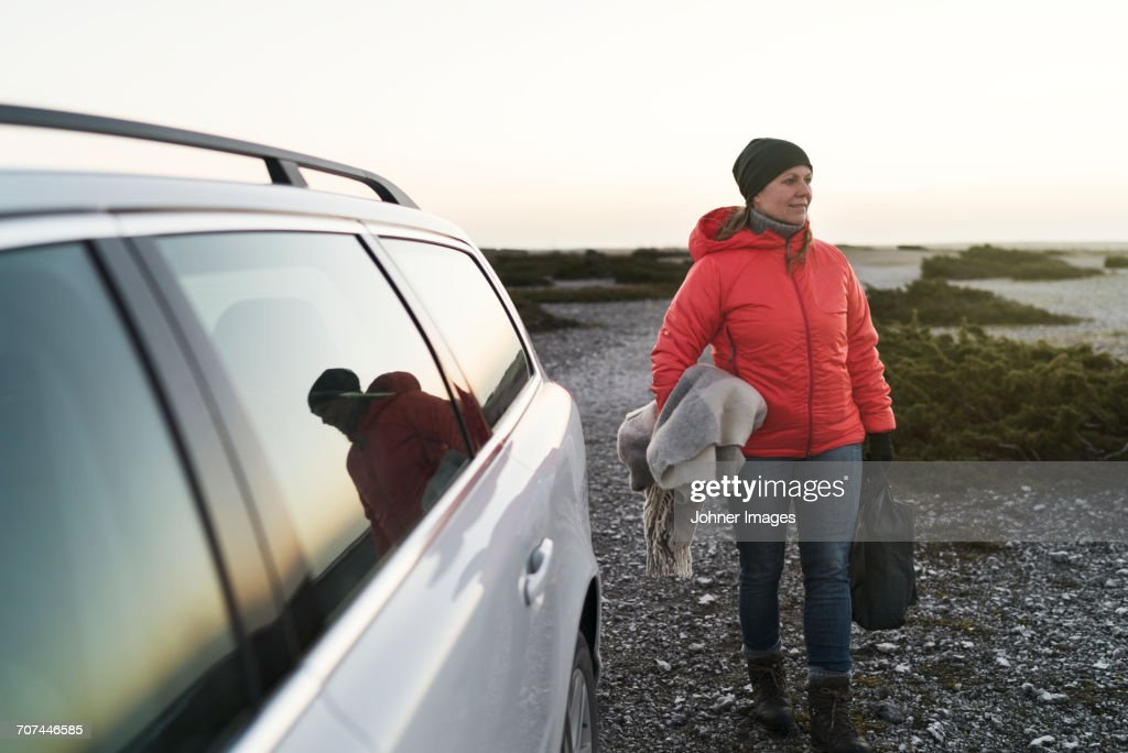 Woman at sea near car : Foto de stock