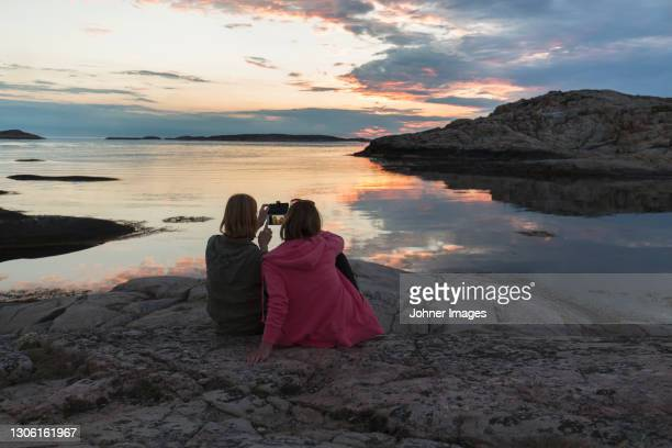 woman at sea taking picture of sunset - sweden stock pictures, royalty-free photos & images