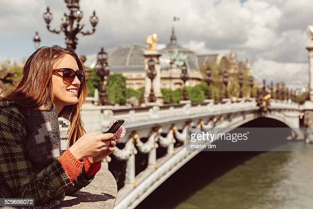 Woman at Seine river texting