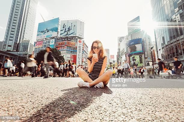 Woman at Shibuya crossing text messaging