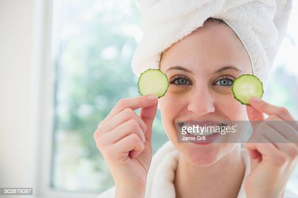 Woman at spa holding cucumber over eyes