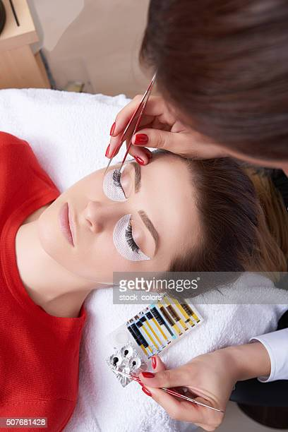 woman at spa salon applying false eyelashes - false eyelash stock pictures, royalty-free photos & images