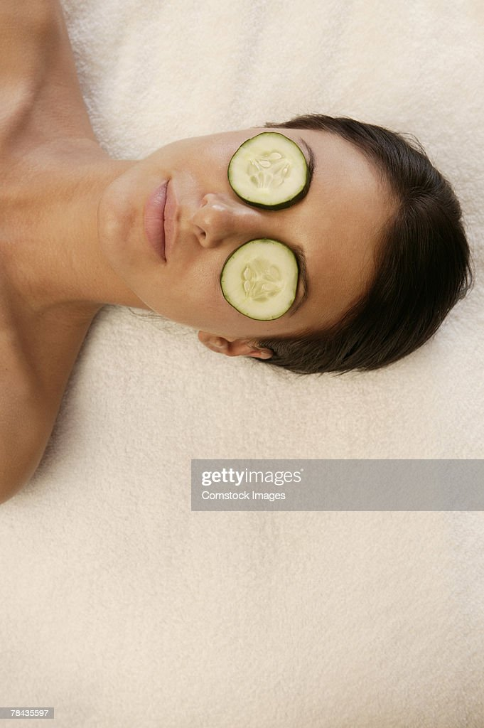 Woman at spa with cucumber slices covering eyes : Stockfoto
