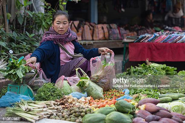 woman at street market selling vegetables, luang prabang, laos, southeast asia - laotian culture stock pictures, royalty-free photos & images