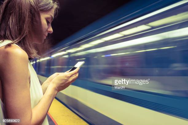 woman at subway station using smartphone to see the map - montreal stock pictures, royalty-free photos & images