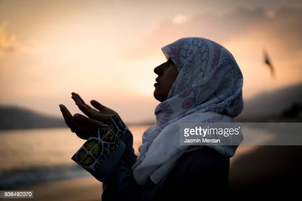 woman at sunset on beach - ramadan stock pictures, royalty-free photos & images