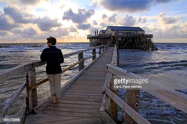 woman at sunset on the beach - sankt peter ording stock-fotos und bilder