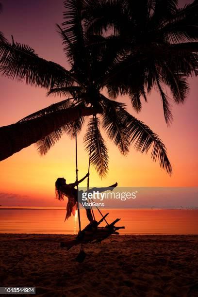 Woman at sunset swing