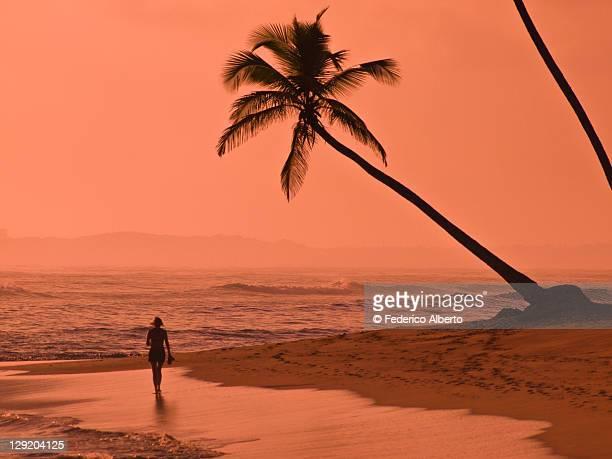 Woman at sunset walking on beach