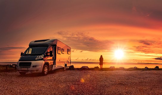 Woman at sunset  with mobile home on the beach 1180017789