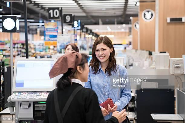 女性のスーパーでは、チェックアウト時に現金をお支払いいただく登録