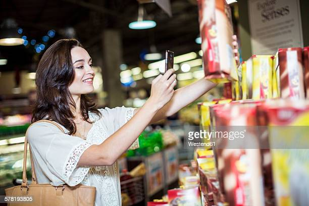 Woman at supermarket scanning prices with her smart phone