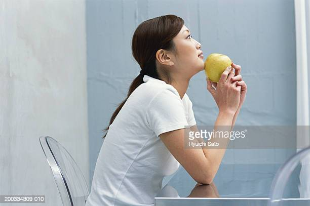 Woman at table holding green apple, side view