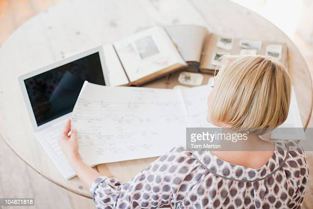 Woman at table looking at genealogical tree