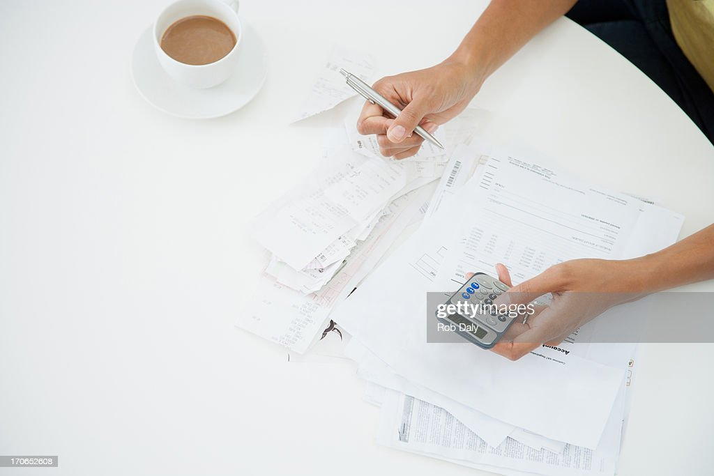 Woman at table paying bills : Stock Photo