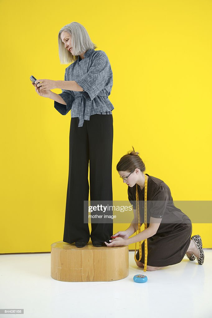 Woman at tailor checking text messages : ストックフォト