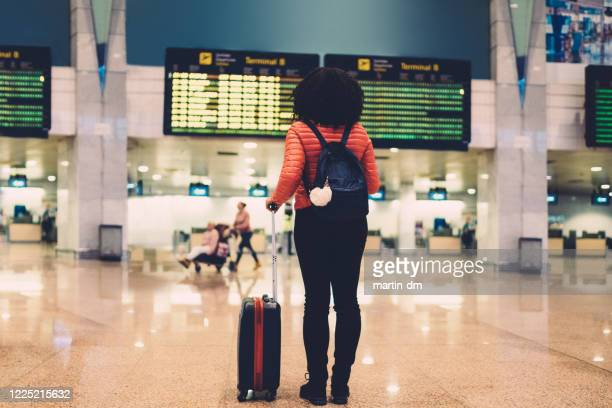 woman at the airport checking the arrival departure board - leaving stock pictures, royalty-free photos & images