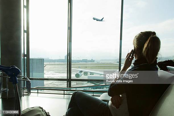 woman at the airport waiting for a fly - abflugbereich stock-fotos und bilder