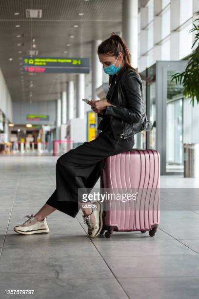 woman at the airport with luggage, wearing n95 face masks - vacations stock pictures, royalty-free photos & images