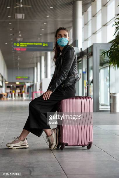 woman at the airport with luggage, wearing n95 face masks - travel stock pictures, royalty-free photos & images